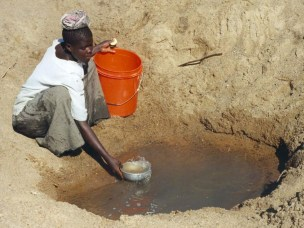 "Mwamanongu Village water source, Tanzania. ""In Meatu district, Shinyanga region, Tanzania, water most often comes from open holes dug in the sand of dry riverbeds, and it is invariably contaminated."""