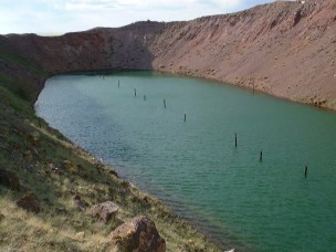 The Tel'kem 2 site, showing the elliptical crater lake produced by the simultaneous detonation of three 0.24 kt fission devices. The crater rim rises up to 25 m above the surface of the water