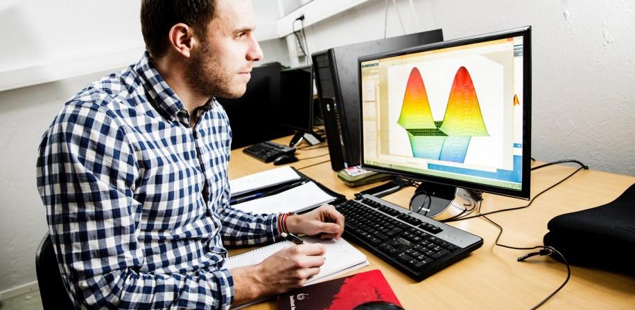 Magnus Oshaug, masterstudent i geomatikk. Illustrasjonen på  dataskjermen er en MathLab grafisk analyse.